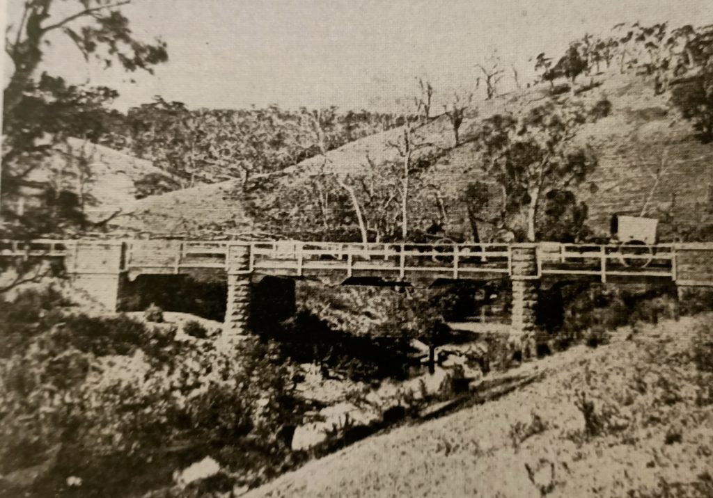 Mccabes Bridge rebuilt on higher level after decking was swept away in 1906 flood. Original bluestone piers remain. Cornelius Francis' covered cart pictured with other unknown cart.