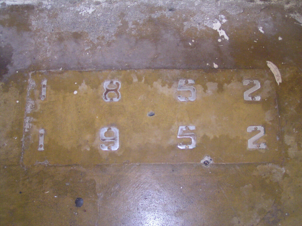 Plaque in concrete floor of house at Mac'sfield